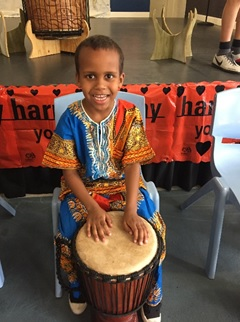 Landyn in his African costume enjoying a turn of the African instruments.